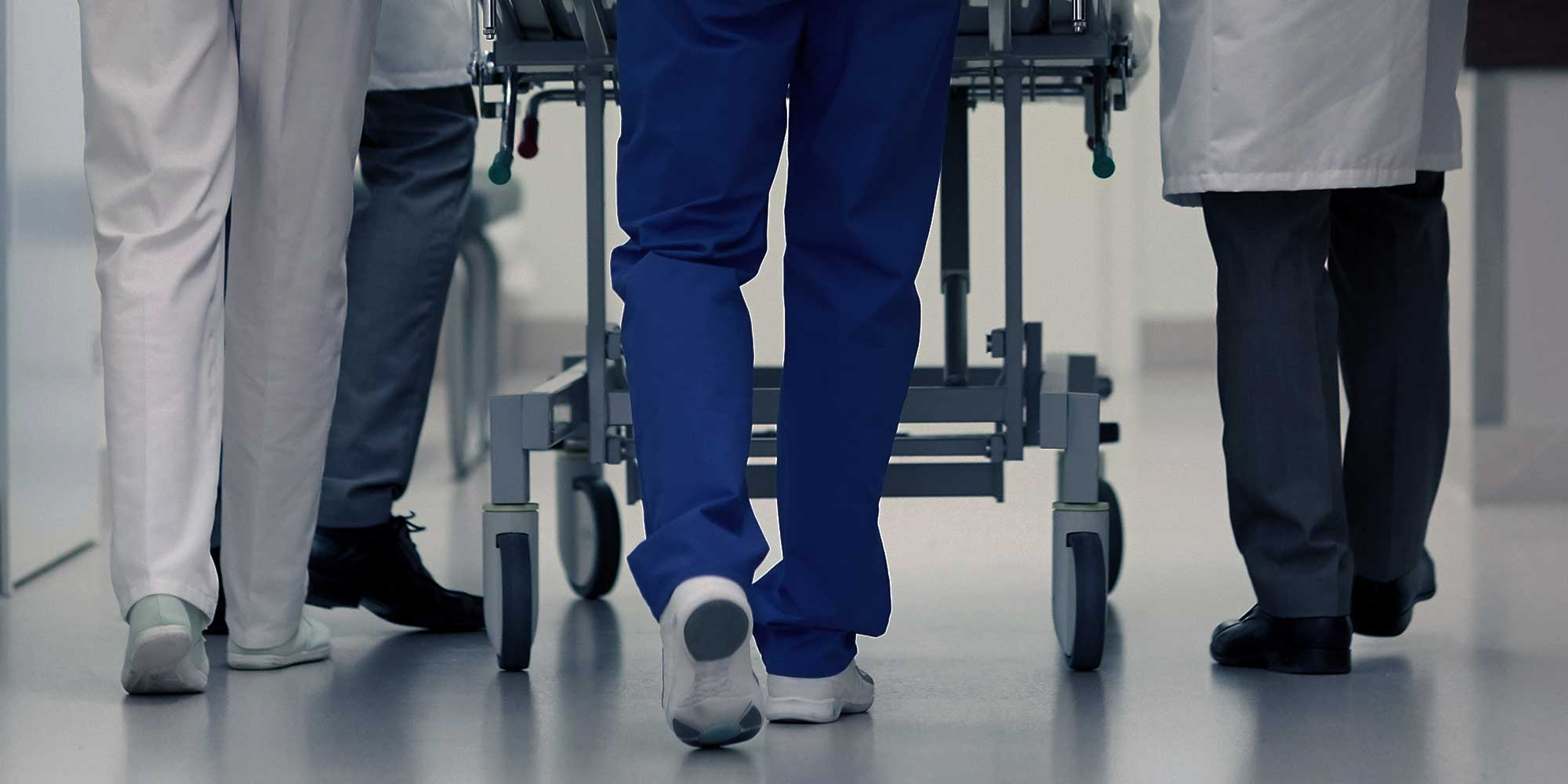 doctors and nurses pushing patient on a hospital trolly